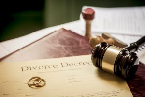 Divorce decree with gavel and rings