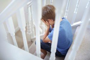 Upset boy on stairs